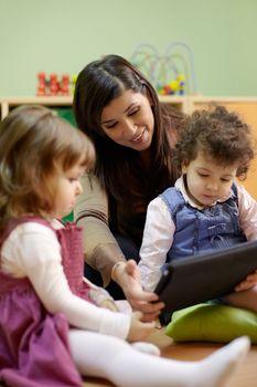 Teacher reading fairy tale to children at school