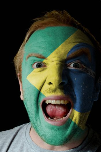 Low key portrait of an angry man whose face is painted in colors of brazilian flag