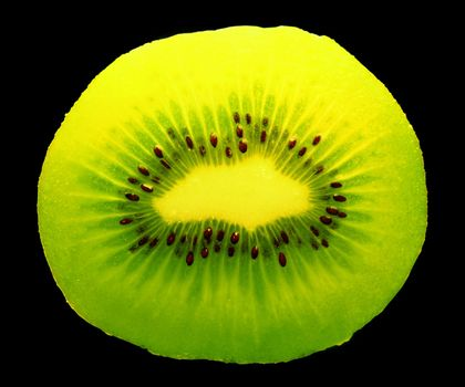 closeup of a kiwi fruit inside with seeds on dark background