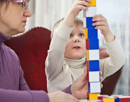 Little blond boy is building tower from colorful blocks