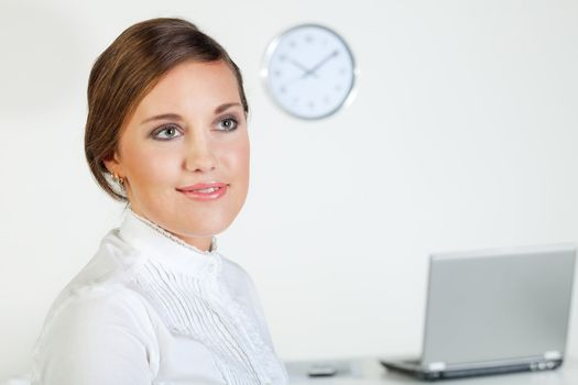 Young pretty smiling businesswoman standing in front of her desk in the office
