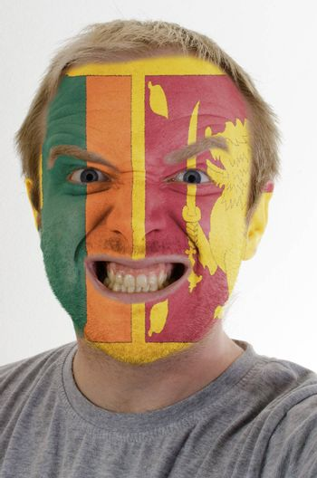 High key portrait of an angry man whose face is painted in colors of srilanka flag