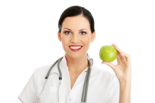 Healthy eating or lifestyle concept. Smiling woman doctor with a green apple.