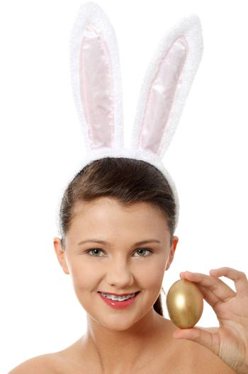 Young girl with bunny ears holding golden egg