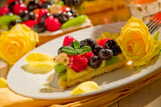 Pie with fruits and petals illuminated by candle light