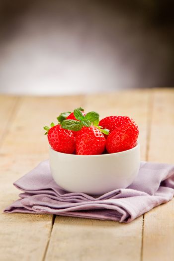 Strawberries on wooden table with violet napkin