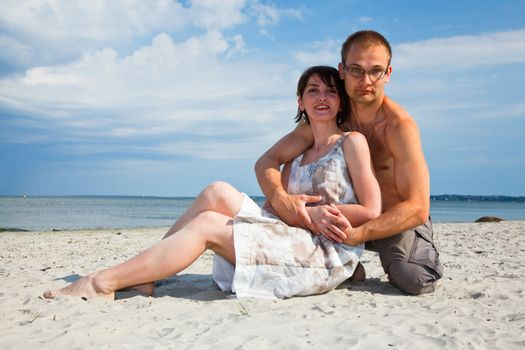 A young couple sitting together on the beach