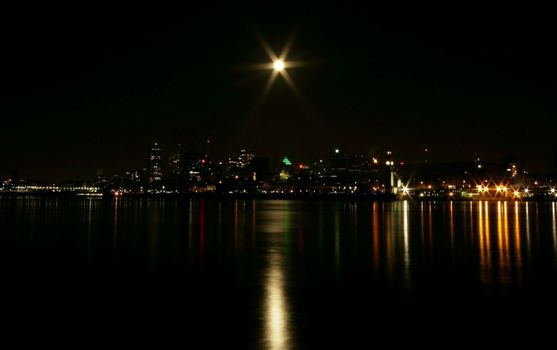 Water edge of Montreal skyline early winter morning with a full moon