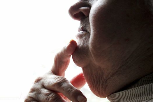 Finger resting on chin of an elderly lady