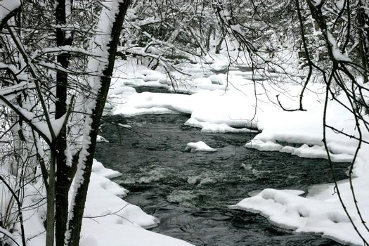 Small rapids on a river bend after a snow storm