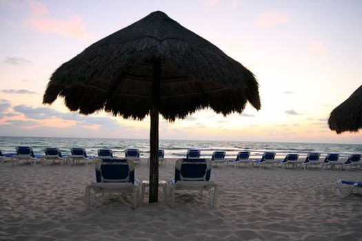 Palapas and chairs before sunrise in Riviera Maya