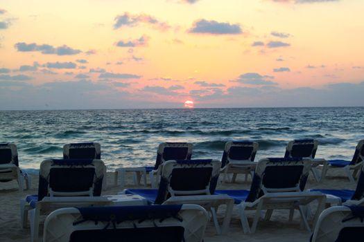 Sunrise over Riviera Maya beach with lounge chairs