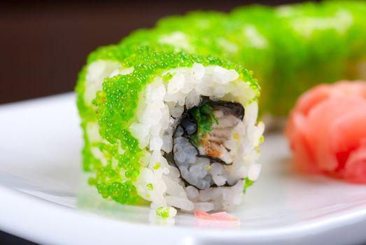 Sushi rolls made of salmon, avocado, flying fish roe - tobiko caviar and philadelphia cheese