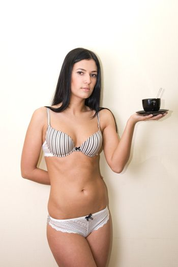 Sexy girl in lingerie at wall background with coffee cup