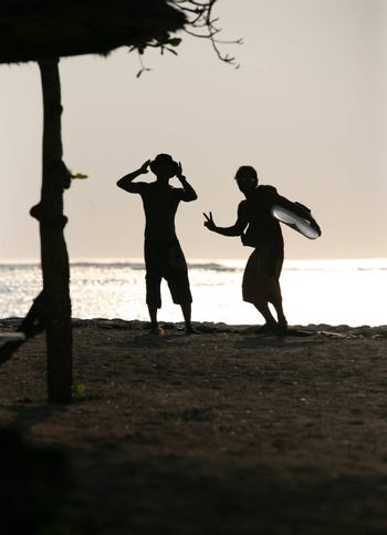 Two men - surfers on a sunset on Bali