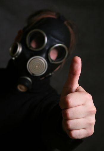 The person in a gas mask. A hand in a zone of sharpness the rest is dim