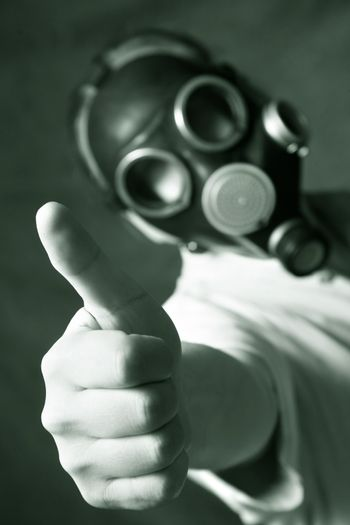 The person in a gas mask. A hand in a zone of sharpness, the rest is dim