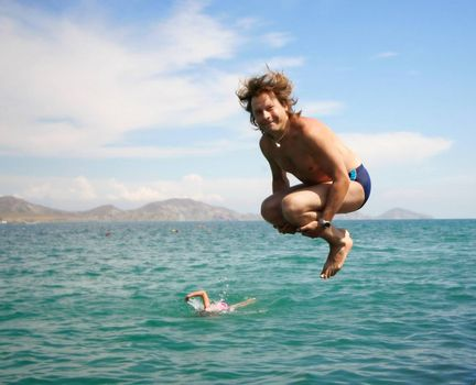 Jumping happy man over water