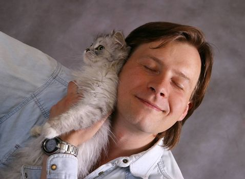 Man covers a kitten on a grey background
