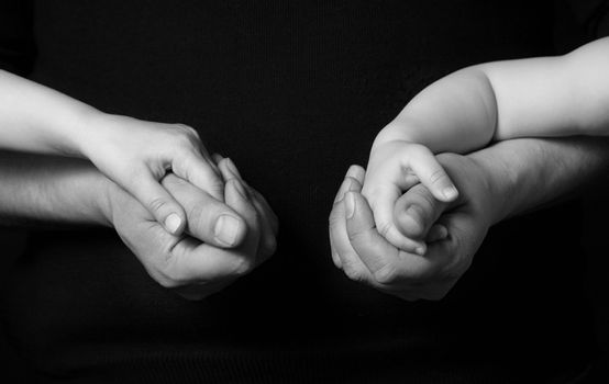 Hands of the father and his daughters on a dark background