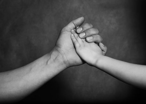 Hand of the adult person and hand of the small child on a dark background