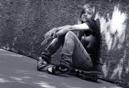 The girl with skateboard sitting against a wall. Shadow on a wall as a wing