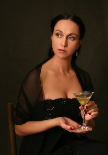 The beautiful woman with a glass of martini on a dark background