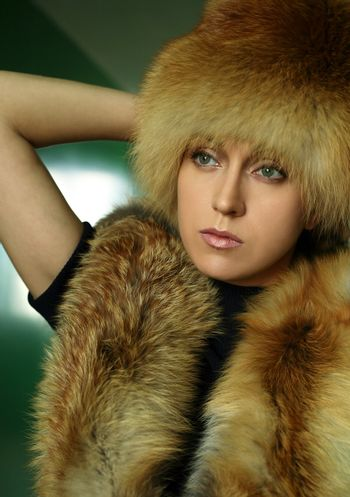 The beautiful woman in a cap and a collar from the fox fur