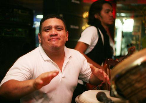 "Smiling musician at an alive concert in a night club ""La vida loka"". Bali. Indonesia"