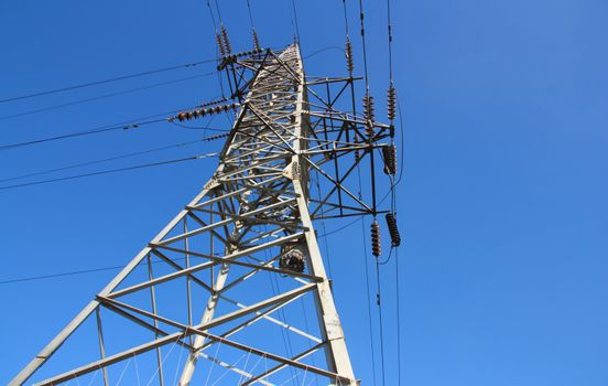 high voltage post against the blue sky