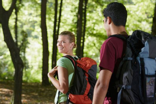 couple with backpack doing trekking in wood