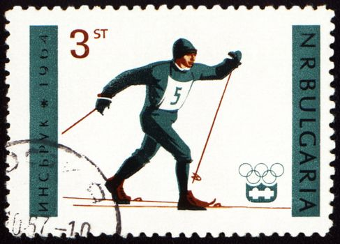 BULGARIA - CIRCA 1964: A post stamp printed in Bulgaria shows running skier, dedicated to the Olympic Winter Games in Innsbruck, series, circa 1964