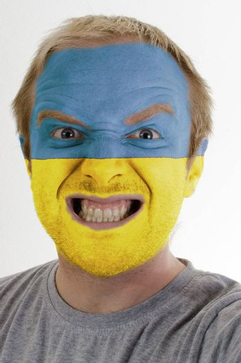 High key portrait of an angry man whose face is painted in colors of ukrainian flag