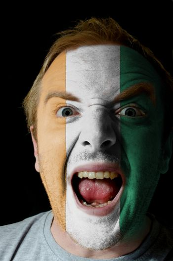 Low key portrait of an angry man whose face is painted in colors of cote ivore flag
