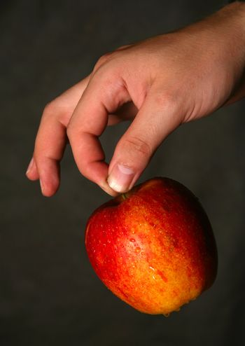 Man's hand with a red apple on a dark background