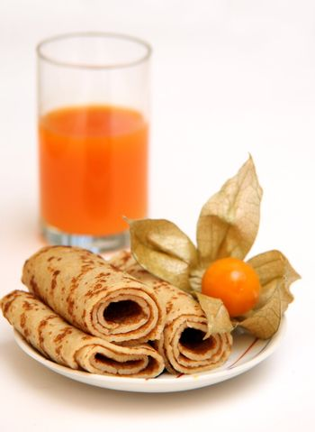 Pancakes on a plate and a glass with carrots juice