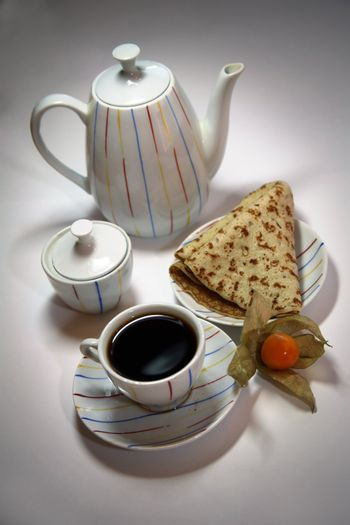 Teapot, cup from coffee and a pancake on a plate, decorated with a yellow berry