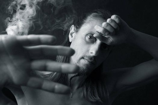 Portrait of the man closed by hands on a background of a smoke
