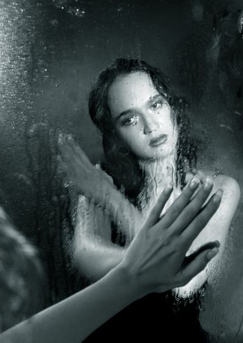 Portrait of the woman in reflection of a wet mirror