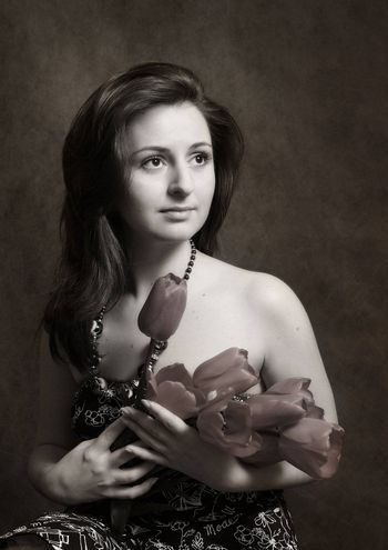 The image of the beautiful girl with tulips in hands