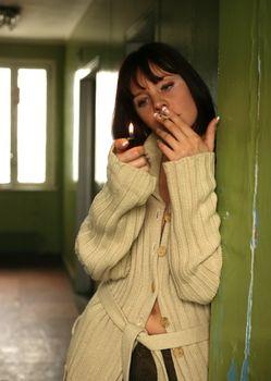 The beautiful brunette gets a light a cigarette