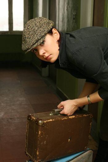 The beautiful woman in a cap with two old suitcases