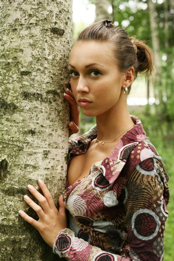 Young woman leaning against birch tree in forest