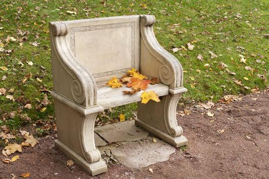 stone park bench with colorful autumn leaves