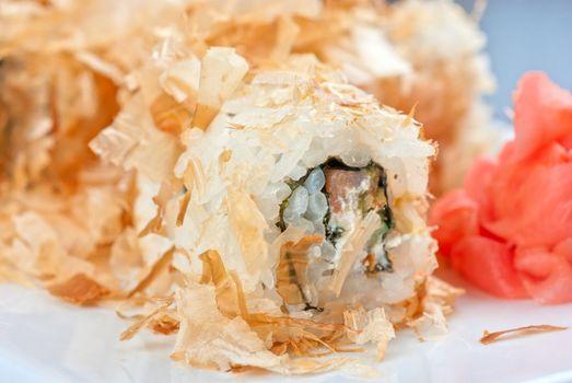 Sushi rolls of rice, nori, cream cheese, avocado, smoked salmon,cucumber and cuts of tuna