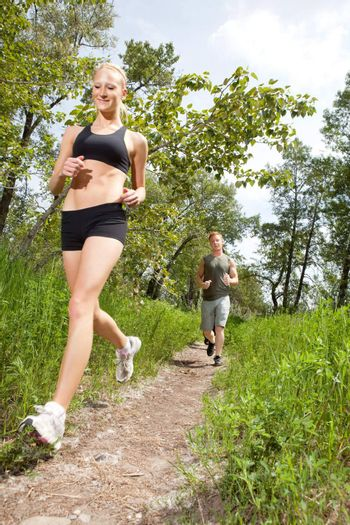 Young man and woman running on a pathway