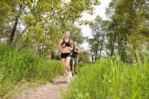 Young friends jogging together outdoors on a trail