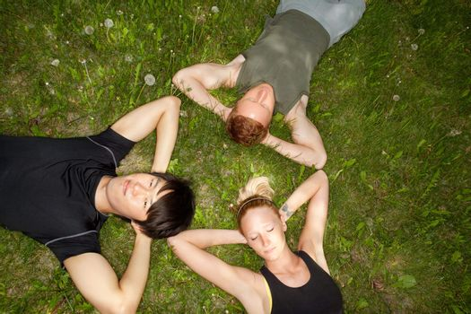 Close-up of friends resting on grass outdoors