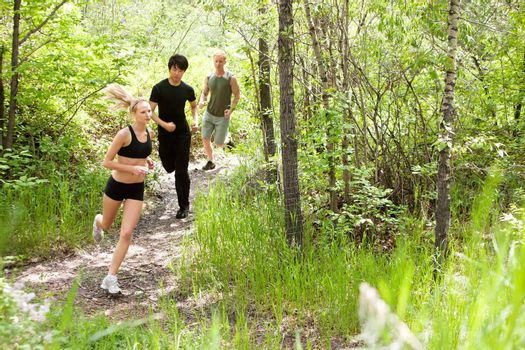 Three friends running in the forest on pathway