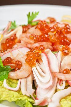 Salad with shrimps, caviar, calamaries, lettuce, lemon and olive